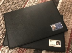 Two black portfolios with business card slots in the front. Business cards for author Mae Clair in slots